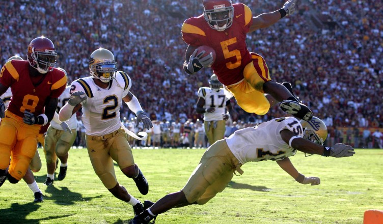 DECEMBER 3, 2005  LOS ANGELES, CA USC's Reggie Bush leaps over UCLA's Marcus Cassel to score a touchdown in Los Angeles.